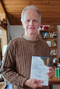 Michael Dolzani standing in a living room holding a copy of his book, The Productions of Time.